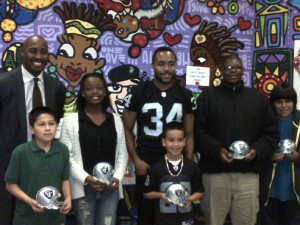 Raiders Safety Mike Mitchell, Mark Urquhart of Kaiser Permanente, and some EOYDC scholars!